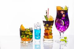 Val av färgrika festliga drinkar, alkoholdrycker och coctailar i eleganta exponeringsglas på vit Royaltyfri Foto