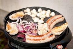 Val av kött som grillar på en elektrisk bärbar grillfest med korvar, champignons och löken Bbq-säsong Fotografering för Bildbyråer