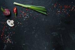 Val av kryddaörter och gräsplaner Ingredienser för matlagning Matbakgrund på svart kritiserar tabellen arkivbilder
