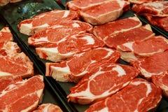 Val av olika snitt av nytt rått mörkt kött i supermarket Arkivbild