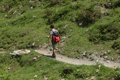 Val d`Aosta, Italy, July 5 2018: male teenager walking alone on a mountain trial. Val d`Aosta, Italy, July 5 2018: male teenager walking alone on mountain trial royalty free stock image