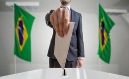 Val eller folkomröstning i Brasilien Väljaren rymmer kuvertet i hand ovanför sluten omröstning Brasilianflaggor i bakgrund Royaltyfri Bild