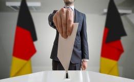 Val eller folkomröstning i Tyskland Väljaren rymmer kuvertet i hand ovanför sluten omröstning Tyskflaggor i bakgrund Royaltyfria Foton