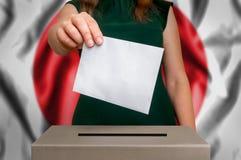 Val i Japan - röstning på valurnan Royaltyfria Foton