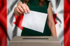 Val i Kanada - röstning på valurnan royaltyfri bild