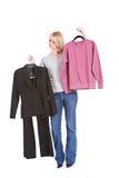 Val: Kvinna som avgör mellan den utsmyckade dräkten eller den lata tröjan Arkivbild