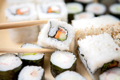 Val upp av ett stycke av sushi med pinnar Royaltyfri Bild