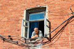 VALAAM, РОССИЯ - 15-ое августа 2015, взгляд старика смотря вне от окна кирпичного здания, 15-ого августа 2015 в VALAAM, РОССИИ Стоковое фото RF