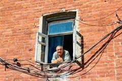VALAAM RYSSLAND - Augusti 15 2015, sikt av en gamal man som ut ser från ett fönster av en tegelstenbyggnad, på Augusti 15 2015 i  Royaltyfri Foto