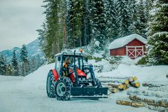 Valdres, Norway - March 26, 2018: Outdoor view of unidentified man in a small truck working, moving the trunks in the Royalty Free Stock Photography