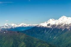 Vale da montanha com picos de montanha neve-tampados Imagem de Stock