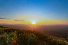 Vale da montanha durante o nascer do sol claro do céu Foto de Stock
