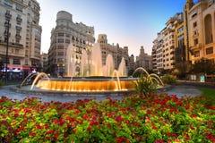 Valence, Espagne - 1er août 2016 : La place d'hôtel de ville au crépuscule, avec les fleurs, sa fontaine majestueuse et les bâtim Photo stock