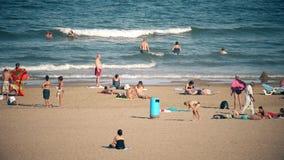 VALENCE, ESPAGNE - 22 SEPTEMBRE 2018 Les gens nageant et prenant un bain de soleil sur la plage arénacée de ville photo libre de droits
