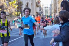 VALENCIA, SPAIN - DECEMBER 2: Runners shake hands with attendees at the XXXVIII Valencia Marathon on December 18, 2018 in Valencia royalty free stock image