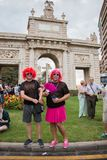 Valencia, Spain - June 16, 2018: Two people in the gay pride day parade in front of a monument with a big cross royalty free stock image