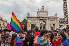 Valencia, Spanien - 16. Juni 2018: Leute in der Parade des homosexuellen Stolzes Tagesvor einem Monument mit einem gro?en Kreuz lizenzfreie stockfotos