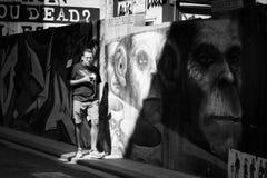 VALENCIA SPANIEN - SEPT 13, 2015: Europeisk man som går i gatan längs en vägg med gatakonst som visar schimpanser Arkivfoto