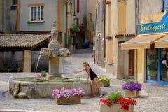 Valensole - den centralt fyrkanten med springbrunnen och privat shoppar Arkivfoton