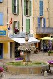 Valensole - den centralt fyrkanten med springbrunnen och privat shoppar Arkivbild
