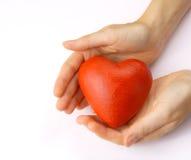 Valentijnskaarten - rood hart in handen stock fotografie