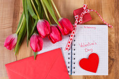 Valentijnskaartendag die in notitieboekje, verse tulpen, liefdebrief, gift en hart, decoratie voor Valentijnskaarten wordt geschr Royalty-vrije Stock Foto's