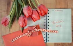 Valentijnskaartendag die in notitieboekje, verse tulpen, liefdebrief, gift en hart, decoratie voor Valentijnskaarten wordt geschr Stock Foto