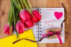 Valentijnskaartendag die in notitieboekje, verse tulpen, liefdebrief, gift en hart, decoratie voor Valentijnskaarten wordt geschr Royalty-vrije Stock Foto