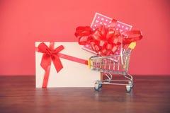 Valentijnskaartendag het winkelen en de Giftdoos van de Giftkaart/Roze huidige doos met rode lintboog op boodschappenwagentje royalty-vrije stock foto's