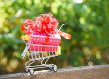 Valentijnskaartendag het winkelen en de huidige doos van de Giftdoos met rode lintboog op boodschappenwagentje Online het Winkele stock foto