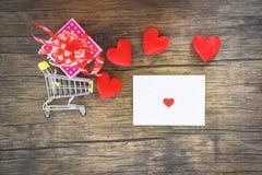 Valentijnskaartendag het winkelen en de rode doos van de hartgift op boodschappenwagentje en Envelopliefdepost Valentine Letter royalty-vrije stock afbeelding