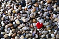 Valentijnskaartenhart op bed van kiezelstenen Stock Foto