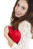 Valentijnskaartenvrouw die een rood hart in haar wapens houden Stock Afbeeldingen