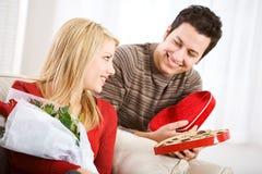 Valentim: A mulher obtém doces e flores no dia de Valentim imagem de stock