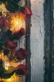 Valentim: Rosas vermelhas e ampolas no fundo de madeira rústico Imagens de Stock Royalty Free