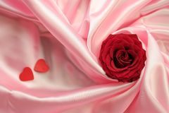 Valentin. A detail of a red rose and two little red hearts lying on pink satin fabric Royalty Free Stock Images