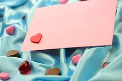 Valentin Card. Valentine's Day theme - a pink valentine card lying on blue satin fabric with little hearts of different materials Stock Photography