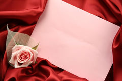 Valentin Card - Red and Pink. A detail of a pink rose with an empty pink card lying on dark red satin fabric Royalty Free Stock Images