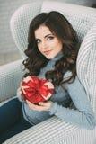 Valentin dag - drömma den gulliga kvinnan med röd hjärta i händer Royaltyfria Bilder