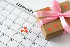 Valentin dag, Februari 14 på kalendern med röda hjärtor och gåvaasken royaltyfri fotografi