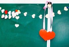 Valentin dag. Hjärta av pappers- hänga på svart tavlabakgrund Royaltyfria Bilder