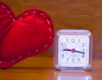 Valentin dag - röd hjärta och en klocka arkivfoto