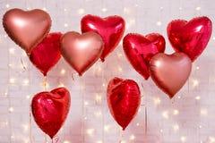 Valentin dagbakgrund - gruppen av röd hjärta formade ballonger över tegelstenväggen arkivfoto