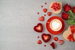 Valentin dagbakgrund med kaffekoppen, hjärtaformchoklad, stearinljus, rosa blommor och gåvaaskar arkivbild