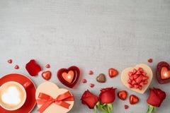 Valentin dagbakgrund med kaffekoppen, hjärtaformchoklad, stearinljus, rosa blommor och gåvor arkivbild