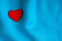 Valentin dagbakgrund. Röd hjärta på blått viker torkduken Arkivbilder