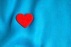Valentin dagbakgrund. Röd hjärta på blått viker torkduken Fotografering för Bildbyråer