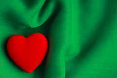 Valentin dagbakgrund. Röd hjärta på gräsplan viker torkduken Arkivbild