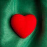 Valentin dagbakgrund. Röd hjärta på gräsplan viker torkduken Fotografering för Bildbyråer