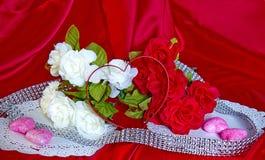 Valentin dagblommor, godis, hjärta Shape på rött silke Royaltyfri Fotografi